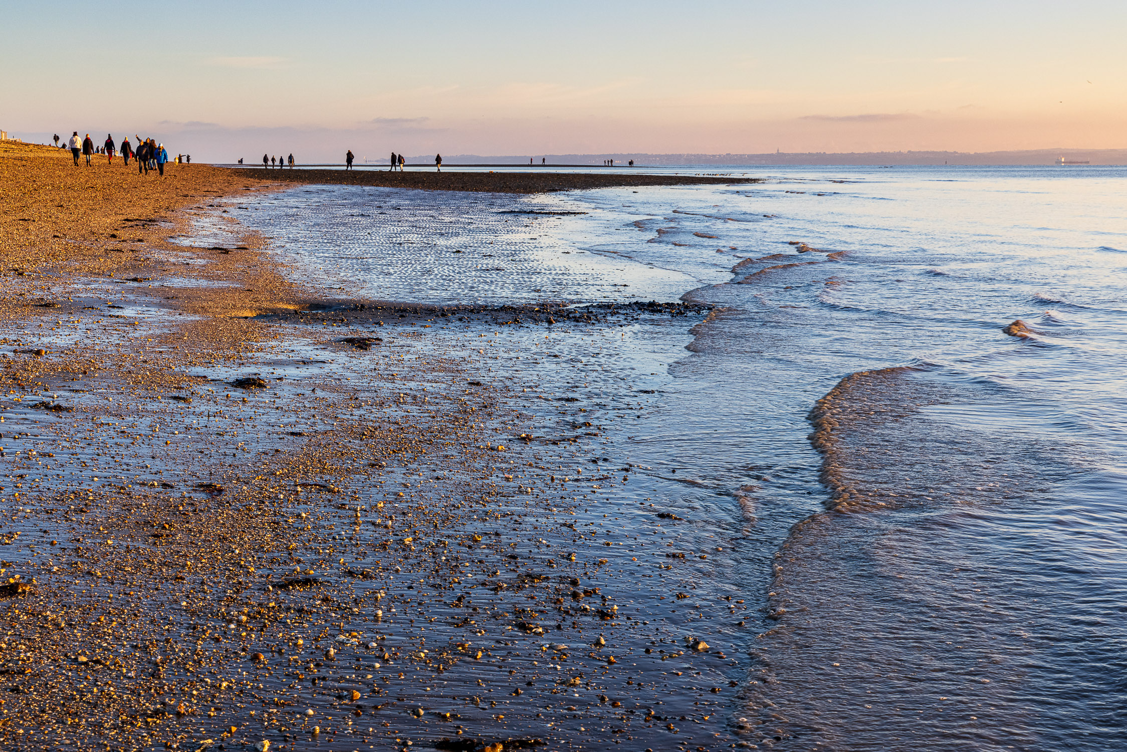 Gentle waves from the receding tide lap the gravel beach at Meon Beach as people take an afternoon stroll on a chill December day.