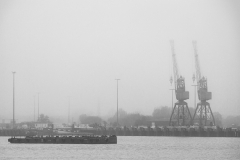 Dock structures emerge from the fog hanging over Southampton Wat